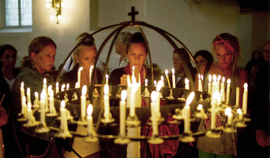 """People light candles at Oslo Cathedral on Sunday in memory of the victims of the attacks on Norway's government headquarters and an island youth retreat. """"We are a people in mourning,"""" Bishop Ole Christian Kvarme said during an emotion-filled Mass attended by members of the Norwegian government, the royal family and the general public. (Associated Press)"""