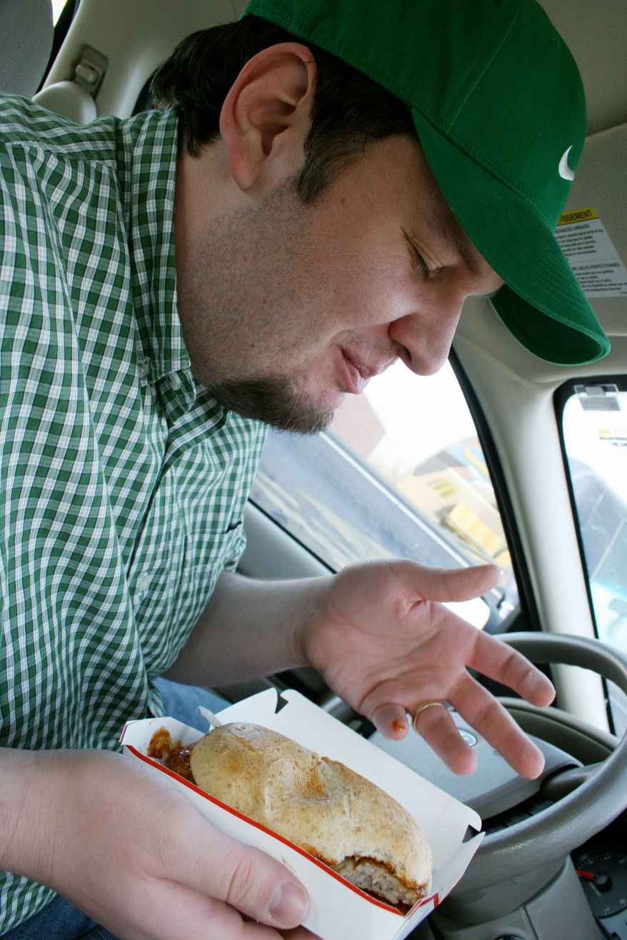 Alan Klein enjoys a McRib. He created the McRib Locator website to help enthusiasts track where McDonald's is offering the elusive sandwich. (Associated Press)