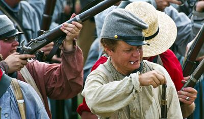 A Confederate infantry soldier reloads her musket. (Drew Angerer/The Washington Times)