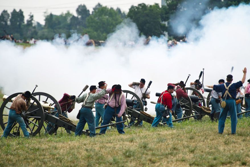 Union artillery units fire their cannons toward the Confederates. (Drew Angerer/The Washington Times)