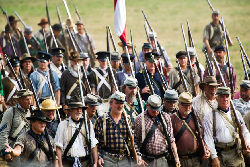 Confederate troops march toward the battlefield during the 150th Anniversary of the Battle of First Manassas/Bull Run Reenactment. (Drew Angerer/The Washington Times)