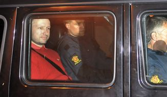 Anders Behring Breivik (left), the suspect in Norway's twin terror attacks, sits in an armored police vehicle after leaving a courthouse following a hearing in Oslo on July 25, 2011. (Associated Press)