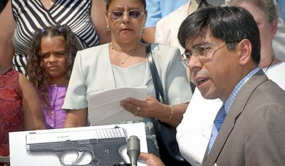 Associated Press Lawyer Hector Pineiro holds a photograph of a Kahr Arms handgun in Worcester, Mass., at the Aug. 15, 2002, announcement of a lawsuit against the gun maker in connection with the December 1999 fatal shooting of Danny Guzman. A settlement of the case was announced Tuesday.