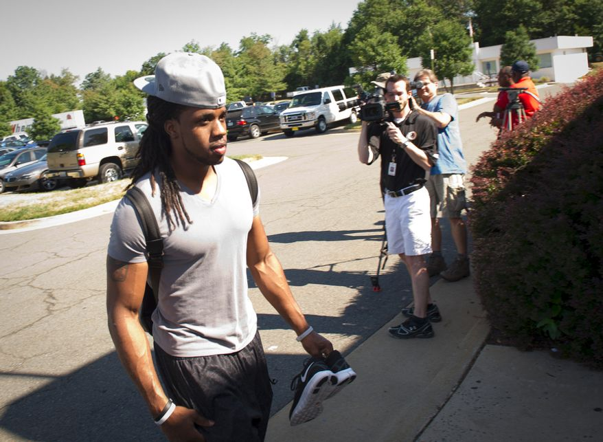 Washington Redskins cornerback Reggie Jones makes his way past reporters and camera crews as he arrives as some of the Washington Redskins players return to Redskins Park in Ashburn, Va., Tuesday, July 26, 2011, a day after the NFL lockout came to an end. (Rod Lamkey Jr./The Washington Times)