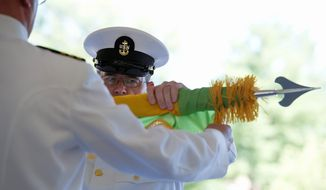"A Navy officer ""cases"" or retires the Armed Forces Institute of Pathology flag during a ceremony Wednesday at Walter Reed Army Medical Center in the District. Formally casing the flags represents the ending of a mission, and for the hospital it ends 102 years of service to American soldiers. (Barbara L. Salisbury/The Washington Times)"