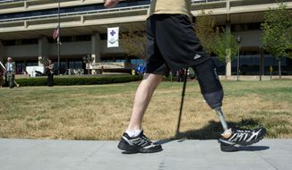 """** FILE ** In this July 27, 2011, file photo, a wounded warrior walks along a sidewalk at Walter Reed during the ceremony to """"case the colors"""" as the wounded and the staff moved to Bethesda or Fort Belvoir. American soldiers """"lost their arms and limbs, but thanks to you they never lost themselves."""" Secretary of the Army John McHugh told the staff. (Barbara L. Salisbury/The Washington Times)"""