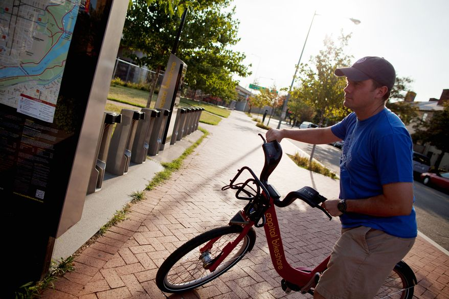 **FILE** Michael Hoffman, 28, of the District, steers a bicycle from the Capital Bikeshare stand near Barracks Row in Southeast. (Pratik Shah/The Washington Times)