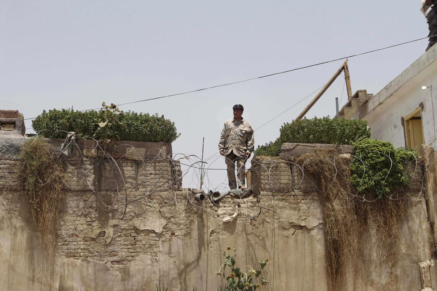 An Afghan border police man stands guard on a wall near the mayor's office in Kandahar south of Kabul, Afghanistan, Wednesday, July 27, 2011. The mayor of Kandahar was assassinated on Wednesday by a suicide bomber who hid explosives in his turban, Afghan officials said. (AP Photo/ Allauddin Khan)