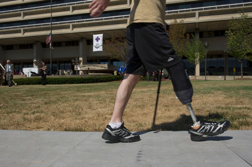 """A wounded warrior walks along a makeshift sidewalk at Walter Reed Army Medical Center Wednesday, July 27, 2011 during a ceremony to officially """"case the colors"""" as a transition to medical services at Bethesda Naval Medical Center and Ft. Belvoir. The Washington, D.C., facility has served wounded warriors and other military personnel and families for more than 100 years. (Barbara L. Salisbury/The Washington Times)"""