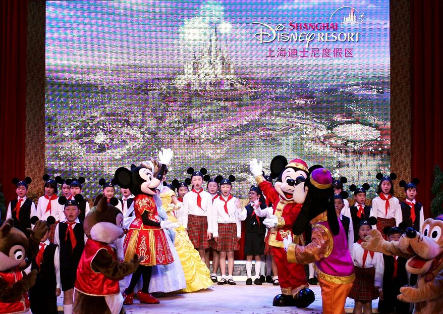 ** FILE ** Walt Disney cartoon characters perform with children during a celebration held for the start of construction work on the Shanghai Disneyland in eastern China.