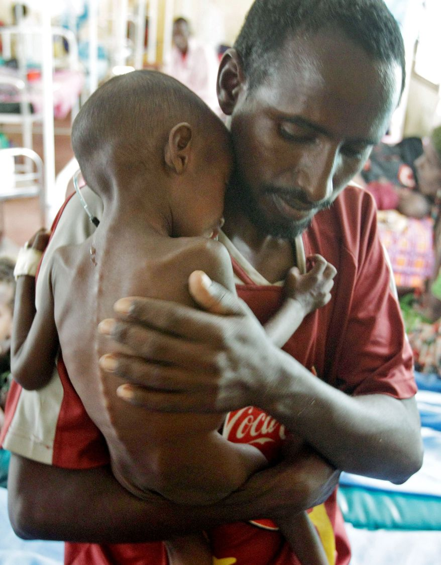 Adam Ibrahim from Somalia is comforted by his father, Abdulle Ibrahim, after treatment at the International Rescue Committee in Kenya on Thursday. Al-Shabab militants have killed men who tried to escape famine with their families.
