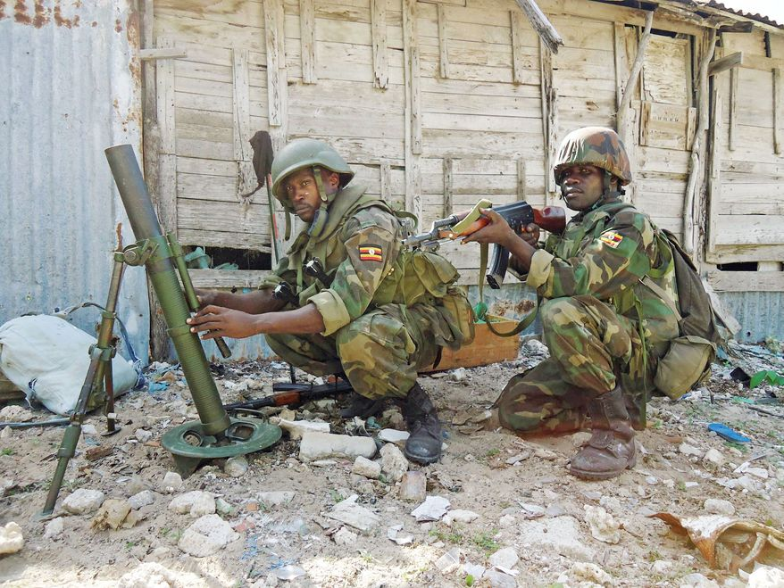 ASSOCIATED PRESS PHOTOGRAPHS African Union troops defend the Yaaqshid district of Mogadishu, Somalia, on Thursday. Spokesman Col. Paddy Ankunda said the AU force believes al-Shabab is trying to prevent aid from reaching tens of thousands of refugees.