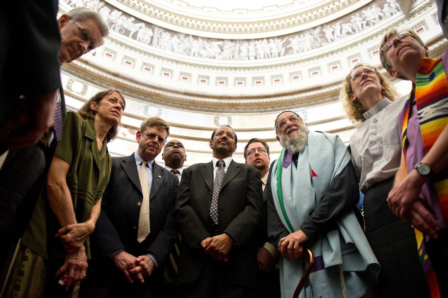 """Calling themselves an """"Interfaith Coalition,"""" a group of religious leaders leads prayer and protest against Congressional leaders in the Capitol Rotunda, on Capitol Hill, in Washington, D.C., Thursday, July 28, 2011. The group said they were against """"immoral budget cuts"""" and said they felt poor people were not being protected by new budget decisions. (Drew Angerer/The Washington Times)"""