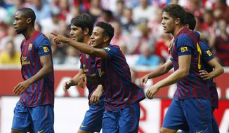 Barcelona's Alcantara Thiago, center, celebrates after scoring against Brazil's SC Internacional de Porto Alegre during their friendly in Munich on Tuesday. Barcelona will play Manchester United on Saturday in a friendly. (AP Photo/Matthias Schrader)