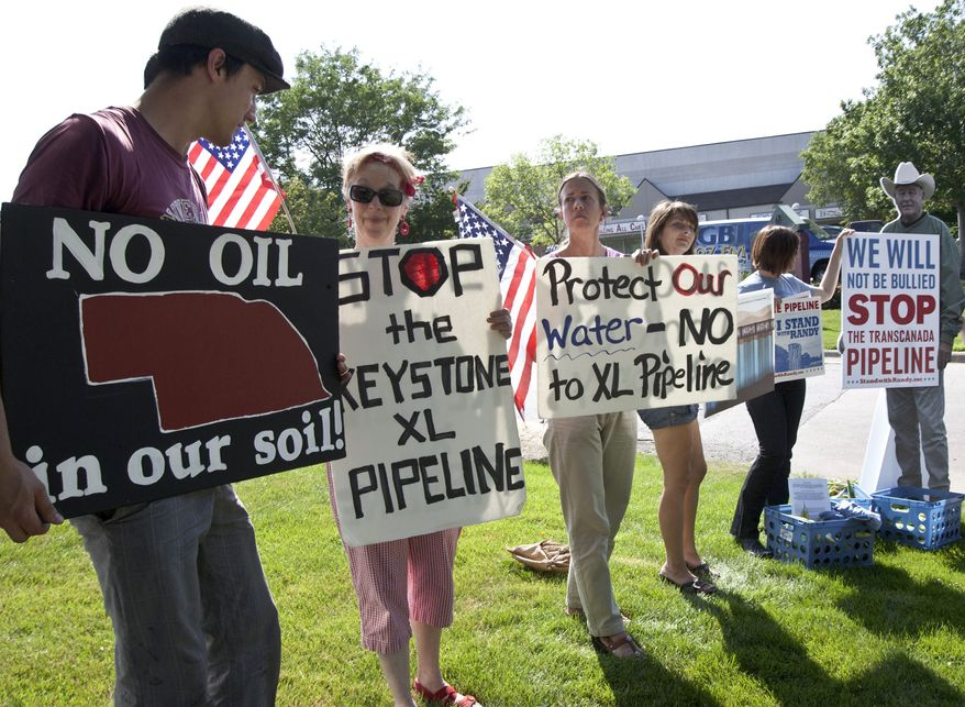 **FILE** Protesters opposed to the Keystone XL pipeline hold signs outside the office of Rep. Lee Terry, Nebraska Republican, in Omaha, Neb., on July 26, 2011. (Associated Press)