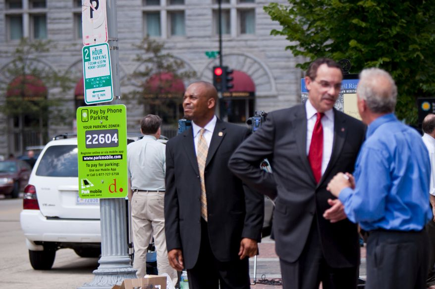 Mayor Vincent C. Gray speaks in front of a Parkmobile sign after an announcement of the completion of pay-by-phone parking across the District. (Pratik Shah/The Washington Times)