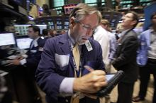 Trader Warren Meyers works on the floor of the New York Stock Exchange on July 29, 2011. (Associated Press)