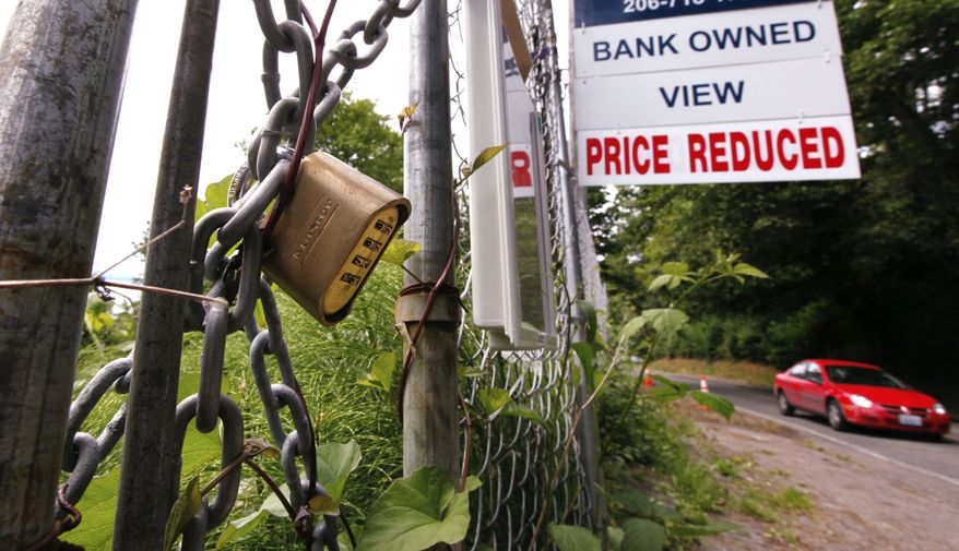 In this photo from June 9, 2011, a bank-owned lot in Seattle is chained and locked but advertised for sale. (Associated Press)