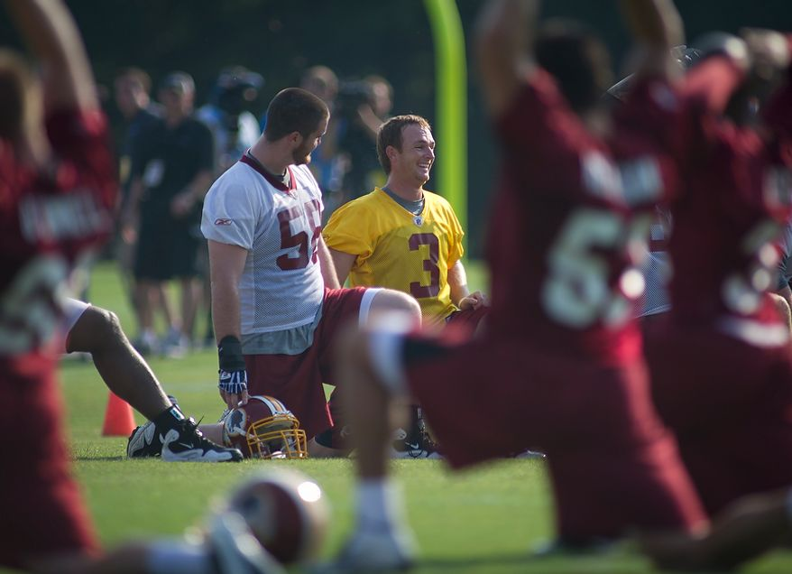 Washington Redskins quarterback John Beck (3) stretches next to center/guard Erik Cook (58) during the first day of training camp at Redskins Park in Ashburn, Va., Friday, July 29, 2011. (Rod Lamkey Jr./The Washington Times)
