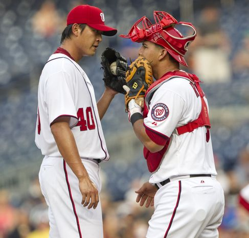 Washington Nationals starting pitcher Chien-Ming Wang talks with catcher Wilson Ramos during the first inning against the Mets. Wang gave up all four of his earned runs in the first inning as the Nats fell to the Mets, 8-5. (AP Photo/Evan Vucci)