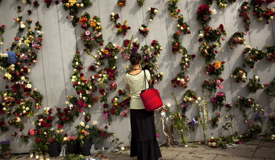 A woman is seen in front of wall decorated with flowers in memory of the victims of Friday's bomb attack and shooting rampage in Oslo, Norway, Tuesday, July 26, 2011. (AP Photo/Emilio Morenatti)