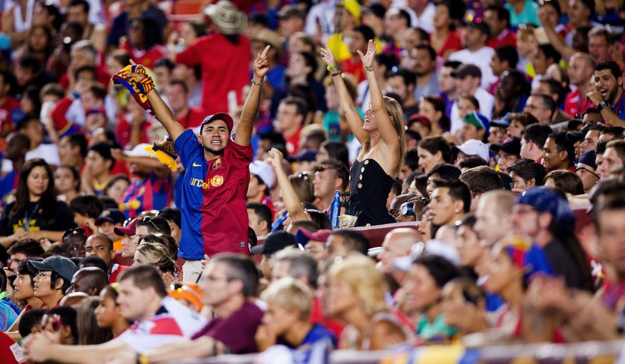 PHOTOGRAPHS BY PRATIK SHAH/THE WASHINGTON TIMES FC Barcelona fans try to pump up the crowd during Saturday night's friendly at FedEx Field, won by Manchester United 2-1. Below, Manchester's Wayne Romney (front) plays a header as Barcelona midfielder Sergio Busquets defends.