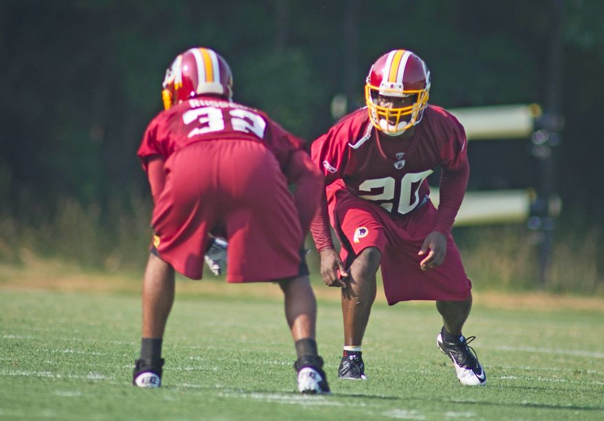 Washington Redskins safety Oshiomogho (20) runs through drills against Anderson Russell (32) during the first day of training camp at Redskins Park in Ashburn, Va., Friday, July 29, 2011. (Rod Lamkey Jr./The Washington Times)