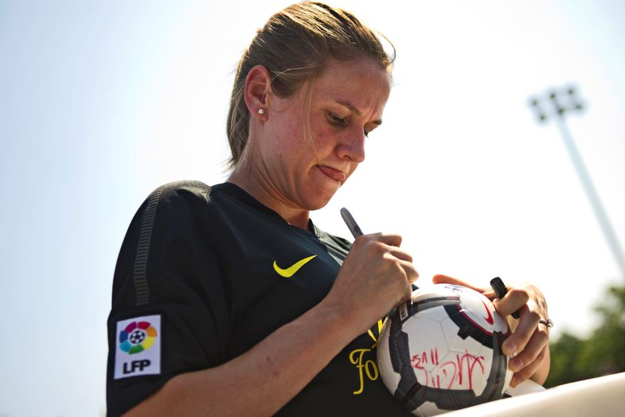 U.S. Soccer player Heather O'Reilly autographs a ball Sunday. Ms. O'Reilly was joined by U.S. teammates Tobin Heath, Ali Krieger and Alex Morgan at a charity soccer match on the Southwest waterfront.