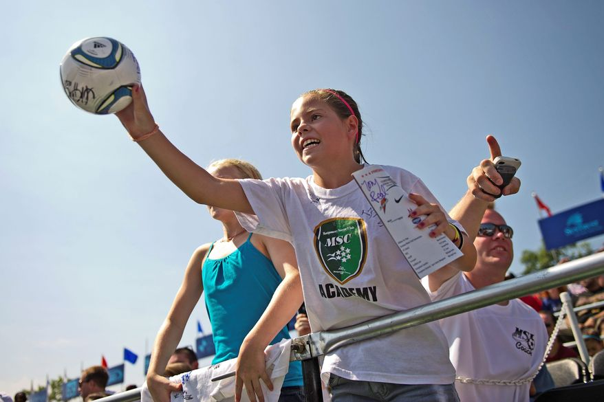 Hoping for an autograph, Isabella Varea of Bethesda extends a ball toward U.S. Soccer player Heather O'Reilly during a charity soccer match Sunday in the District.