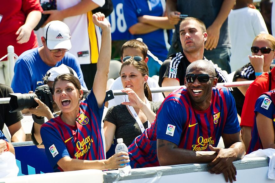 Mia Hamm, left, and Kobe Bryant, right, watch the action from the sidelines during the Mia Hamm and Nomar Garciaparra Celebrity Soccer Challenge, at Washington Kastles Stadium, in Washington, D.C., Sunday, July 31, 2011. (Drew Angerer/The Washington Times)
