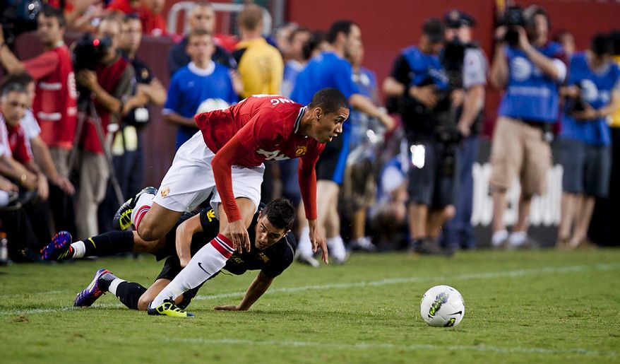 Manchester United defender Chris Smalling dribbles the ball past FC Barcelona forward David Villa during the 2011 Herbalife World Football Challenge match between Manchester United and FC Barcelona at FedEx Field in Landover, Md. on Saturday, July 30, 2011. (Pratik Shah/The Washington Times)