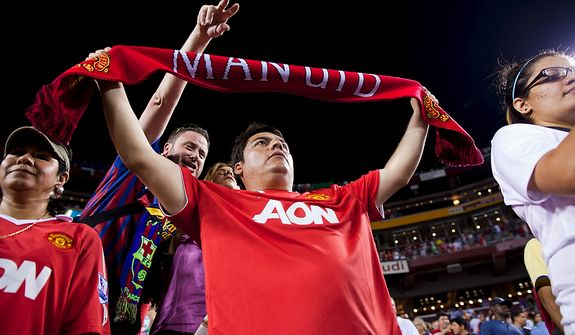 Manchester United fan Juan Corpus of San Antonio, Tx. shows his team spirit around fans of the opposing team during the 2011 Herbalife World Football Challenge match between Manchester United and FC Barcelona at FedEx Field in Landover, Md. on Saturday, July 30, 2011. (Pratik Shah/The Washington Times)