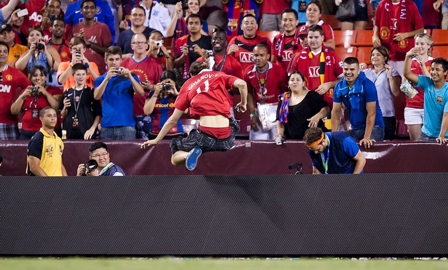 A Manchester United fan jumps over a barrier after running across the field after the 2011 Herbalife World Football Challenge match between Manchester United and FC Barcelona at FedEx Field in Landover, Md. on Saturday, July 30, 2011. (Pratik Shah/The Washington Times)