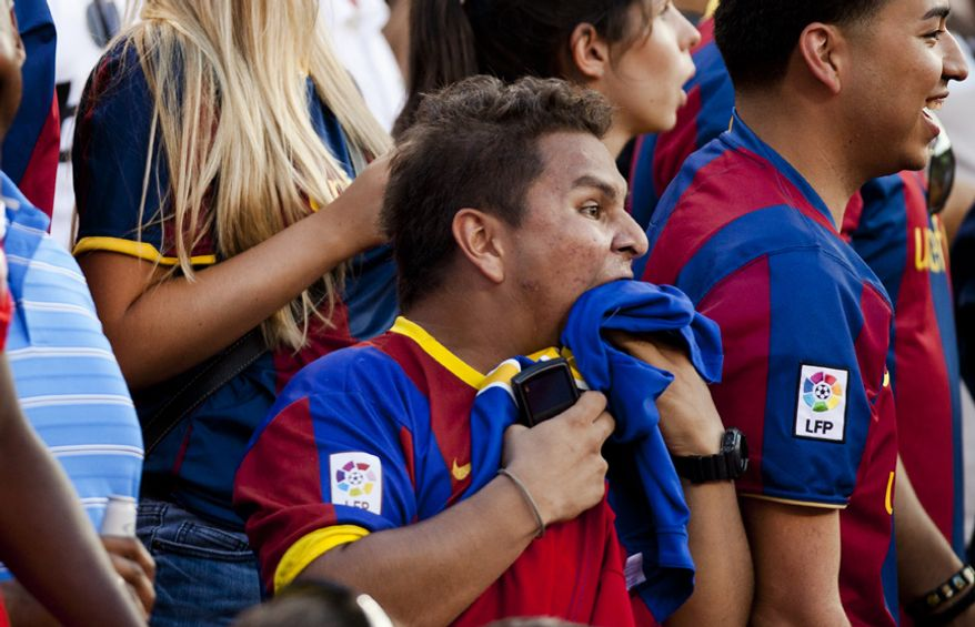 An FC Barcelona fan bites his shirt in frustration after his team missed an opportunity to score a goal during the 2011 Herbalife World Football Challenge match between Manchester United and FC Barcelona at FedEx Field in Landover, Md. on Saturday, July 30, 2011. (Pratik Shah/The Washington Times)