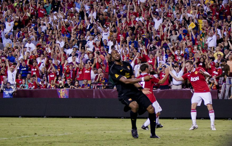 Manchester United forward Michael Owen celebrates with teammate Tom Cleverley after scoring a goal during the 2011 Herbalife World Football Challenge match between Manchester United and FC Barcelona at FedEx Field in Landover, Md. on Saturday, July 30, 2011. (Pratik Shah/The Washington Times)