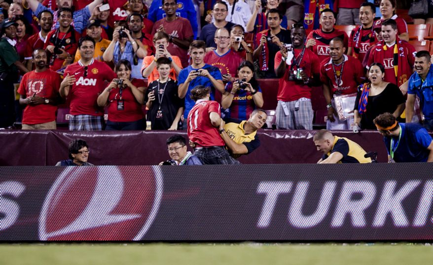 A member of the FedEx Field event staff takes down a Manchester United fan who ran across the field after the 2011 Herbalife World Football Challenge match between Manchester United and FC Barcelona at FedEx Field in Landover, Md. on Saturday, July 30, 2011. (Pratik Shah/The Washington Times)