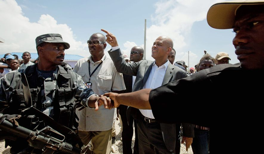 A security detail protects President Michel Martelly (center) as he visits model homes in Port-au-Prince. Haitians are now griping that Mr. Martelly hasn't brought much change during his three months in office. Many young people who supported him are now having second thoughts. (Associated Press)