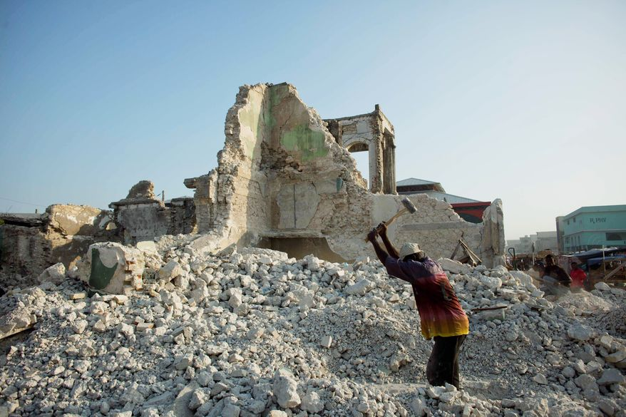 A man works in the ruins of a building in Port-au-Prince damaged by an earthquake. The government is giving wage earners access to credit at a preferential rate for 10 years to enable them to buy or construct a home. (Associated Press)