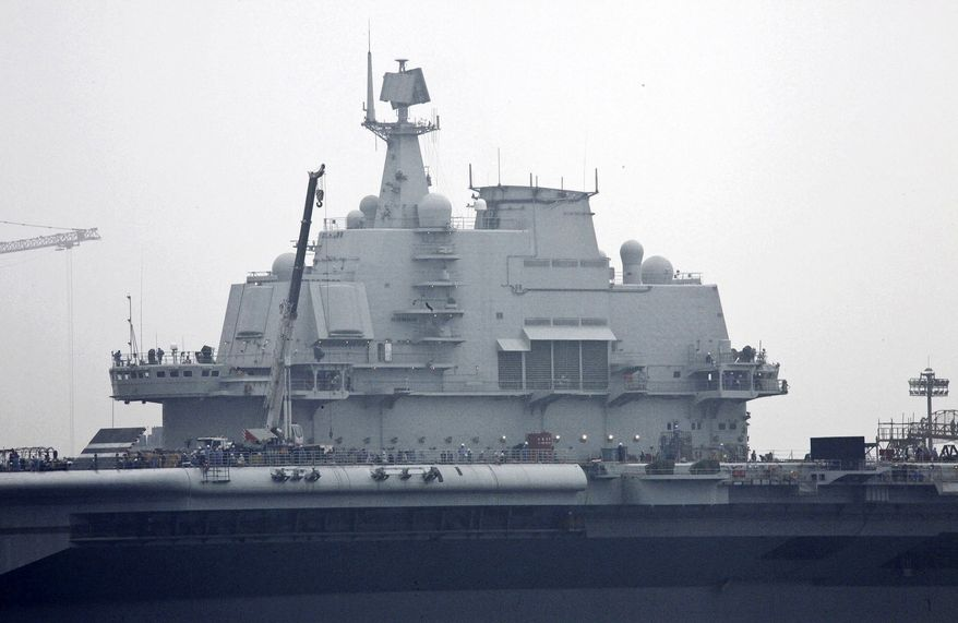 """Workers are seen on the flight deck of China's first aircraft carrier, the former """"Varyag"""" of Ukraine, which is under restoration at a shipyard in northeastern China's Liaoning province. China has acknowledged it is rebuilding an aircraft carrier bought more than a decade ago, but says the refurbished ship will be used only for research and training - a strong indication it plans to build carriers of its own. (AP Photo/Color China Photo)"""