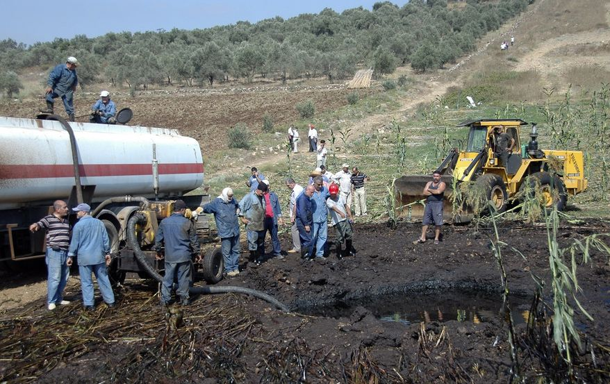 """** FILE ** In this photo released by the Syrian official news agency SANA, workers pump oil from the site of a bomb blast that struck a major oil pipeline in the western town of Talkalakh, Syria, Friday, July 29, 2011. Syrian state television described the blast as a """"terrorist"""" attack, saying that a group of """"saboteurs"""" was behind the explosion. (AP Photo/SANA)"""