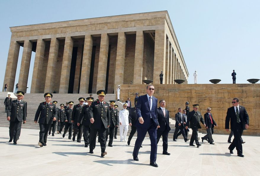 Prime Minister Recep Tayyip Erdogan (in business suit, front-center) leads a group of military officers away from the mausoleum of modern Turkey's founder Kemal Ataturk on Monday after the military's annual meeting in the capital of Ankara. (Associated Press)