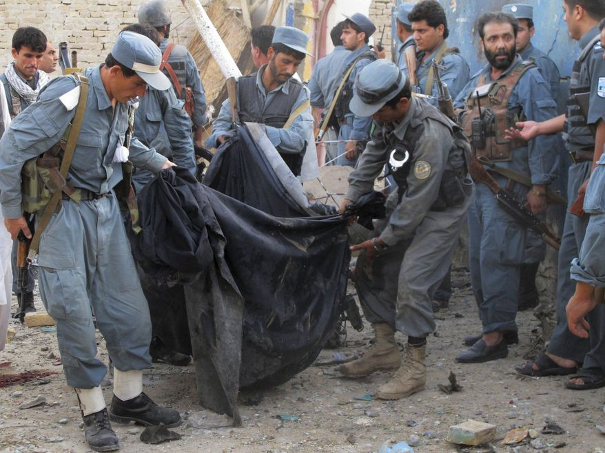 Afghan police officers carry the body of a hotel guard in a black cloth after a suicide attack in Kunduz, north of Kabul, Afghanistan, on Aug. 2, 2011. (Associated Press)