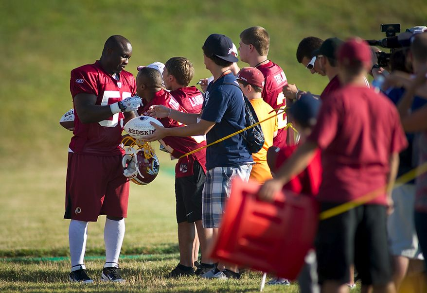 Washington Redskins linebacker London Fletcher (59) signs autographs as he makes his way to the practice field during training camp at Redskins Park in Ashburn, Va., Tuesday, August 2, 2011. (Rod Lamkey Jr./The Washington Times)