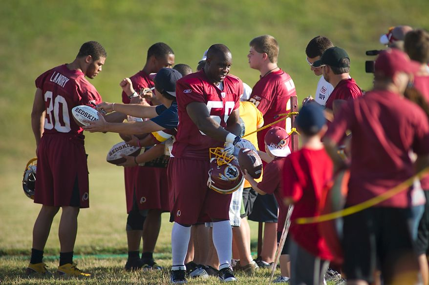 Washington Redskins linebacker London Fletcher (59) and safety LaRon Landry (30) sign autographs as they make their way to the practice field during training camp at Redskins Park in Ashburn, Va., Tuesday, August 2, 2011. (Rod Lamkey Jr./The Washington Times)