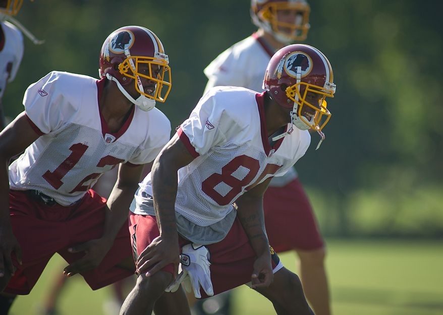 Washington Redskins wide receivers Malcolm Kelly (12) and Leonard Hankerson (85) work out with stretching exercises during training camp at Redskins Park in Ashburn, Va., Tuesday, August 2, 2011. (Rod Lamkey Jr./The Washington Times)