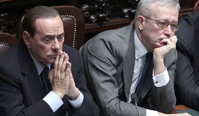 Italian Premier Silvio Berlusconi, left, flanked by Finance Minister Giulio Tremonti, reacts after addressing the Parliament on the state of the economy in Rome, Wednesday, Aug. 3, 2011. (AP Photo/Gregorio Borgia)