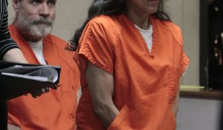 ** FILE ** In this June 2, 2011, file photo, Nancy Garrido takes a seat as her husband, Phillip Garrido, background, looks on at the El Dorado County Superior Court in Placerville, Calif. (AP photo/Rich Pedroncelli, Pool, File)