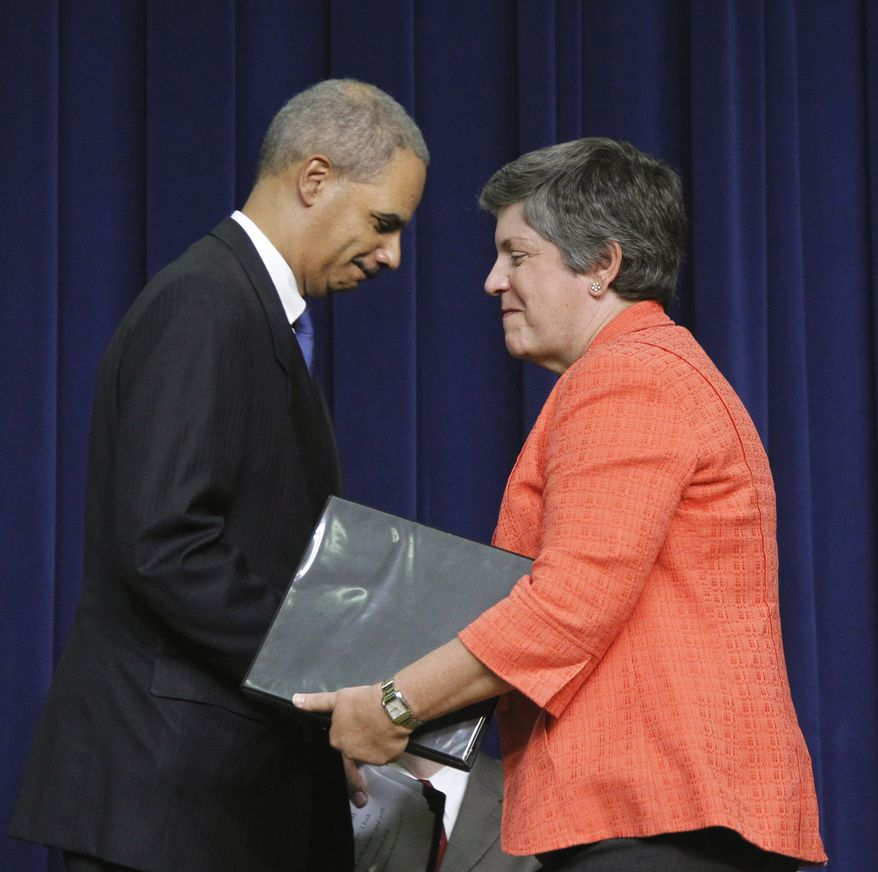 **FILE** Homeland Security Secretary Janet Napolitano (right) is greeted by Attorney General Eric Holder during the launching of the Strategy to Combat Transnational Organized Crime on July 25, 2011, at the White House. (Associated Press)