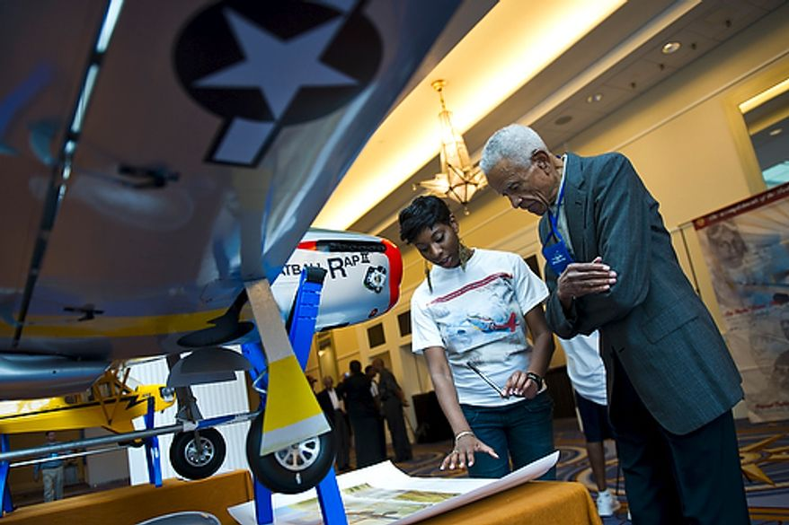 "Dr. Donald Jackson, a bomber pilot and original Tuskegee Airman, prepares to sign a commemorative Tuskegee Airmen poster on the first day of the 40th Annual Tuskegee Airmen National Convention, at the Gaylord Hotel and Convention Center, in National Harbor, Md., Wednesday, Aug. 3, 2011. At left is convention volunteer Linze Greene, from Dallas. Her father and great uncle were both original Tuskegee Airmen. ""You see these other guys here and it just does something wonderful for your human  psyche,"" said Dr. Jackson, who is making his 6th trip to the convention this year. (Drew Angerer/The Washington Times)"