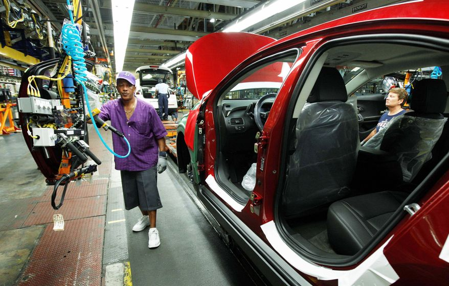 Assembly line worker Edward Houie moves a door into position for a 2012 Chevrolet Volt at the General Motors Hamtramck Assembly plant in Hamtramck, Mich. GM said Thursday that its second-quarter profit nearly doubled to $2.5 billion as automaker got higher prices for its cars and trucks worldwide. (Associated Press)